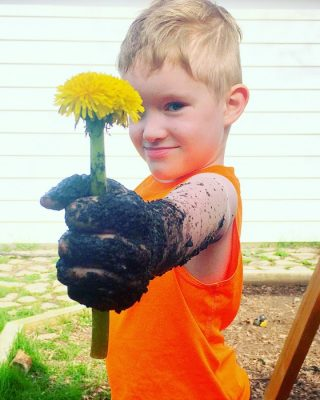 Liam holding muddy flower